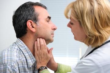 доктор осматривает щитовидку у мужчины